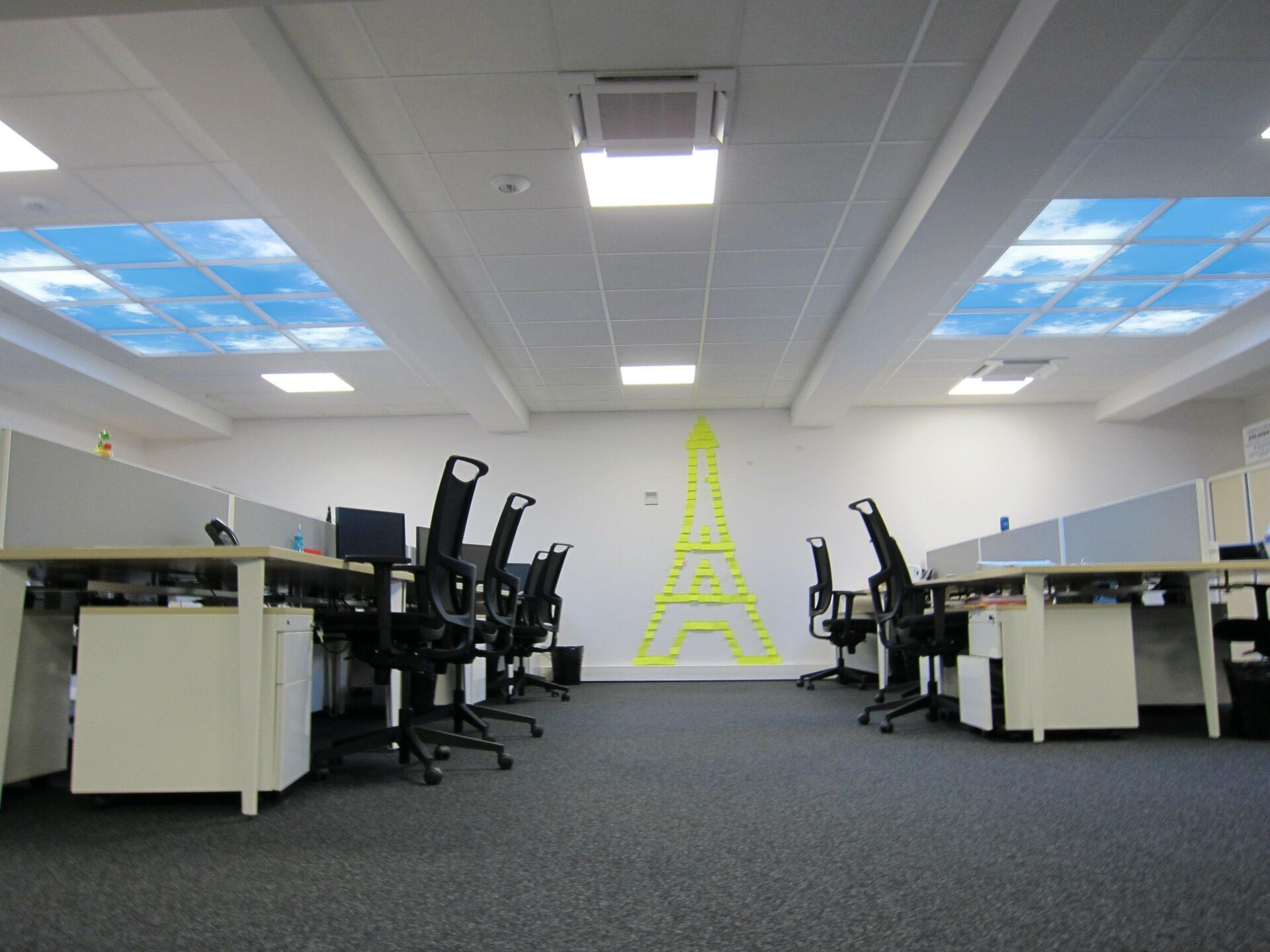 2 plafonds lumineux Cumulux 180x240 cm pour un open space sombre.