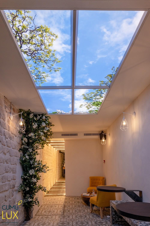 Faux plafond circadien avec quatre pavé led ciel Cumulux, pour une salle de restauration sombre.