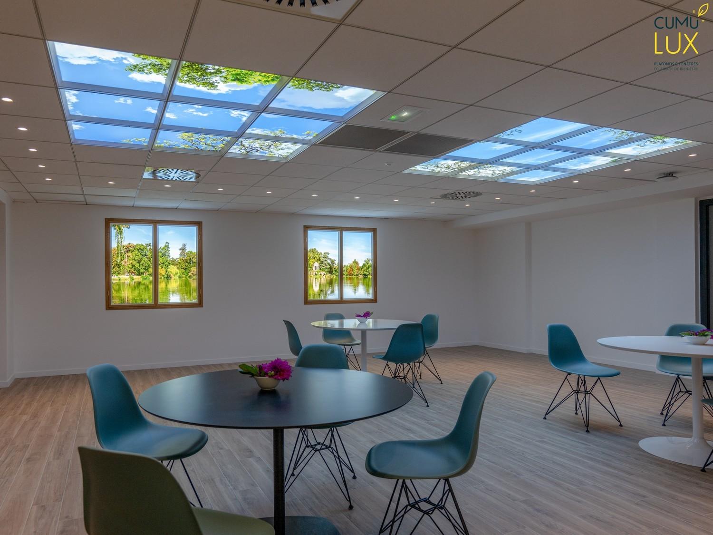 Plafonds lumineux et fenêtres virtuelles Cumulux dans une salle de restauration privée de lumière naturelle chez Interfel