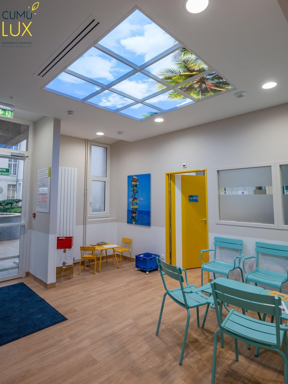 Faux plafond LED ciel Cumulux pour éclairer une salle d'attente sombre pour enfants.